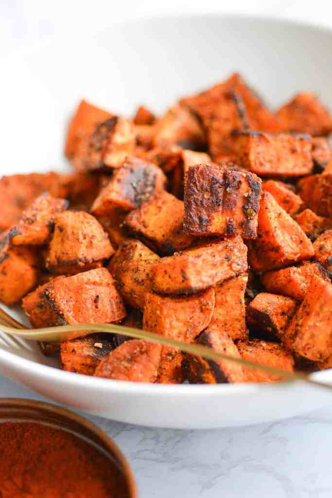 Close up of a white bowl filled with breakfast sweet potatoes