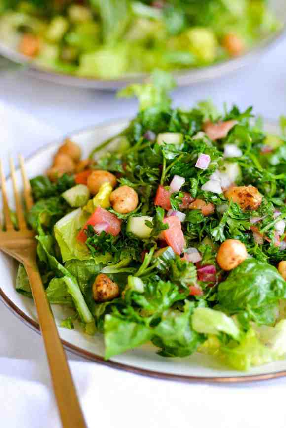 Salad with Tabbouleh on top on a tan plate with a gold fork