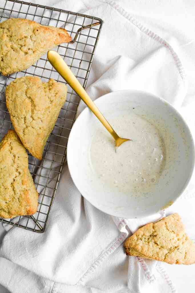 Vanilla Bean glaze in a white bowl with a gold spoon next to scones on a wire cooling rack
