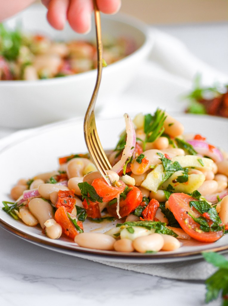 Hand holding a gold fork picking up vegan cannellini bean salad