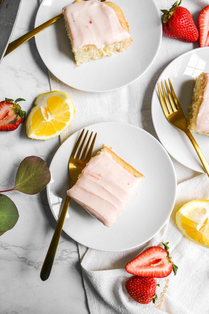 Overhead shot of 3 plates of lemon cake with cream cheese frosting with greenery and strawberries