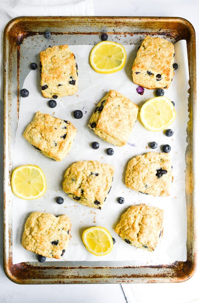Eggless scones on a baking sheet with blueberies and lemon slices