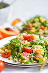 two plates of salad with peaches, tomatoes and arugula