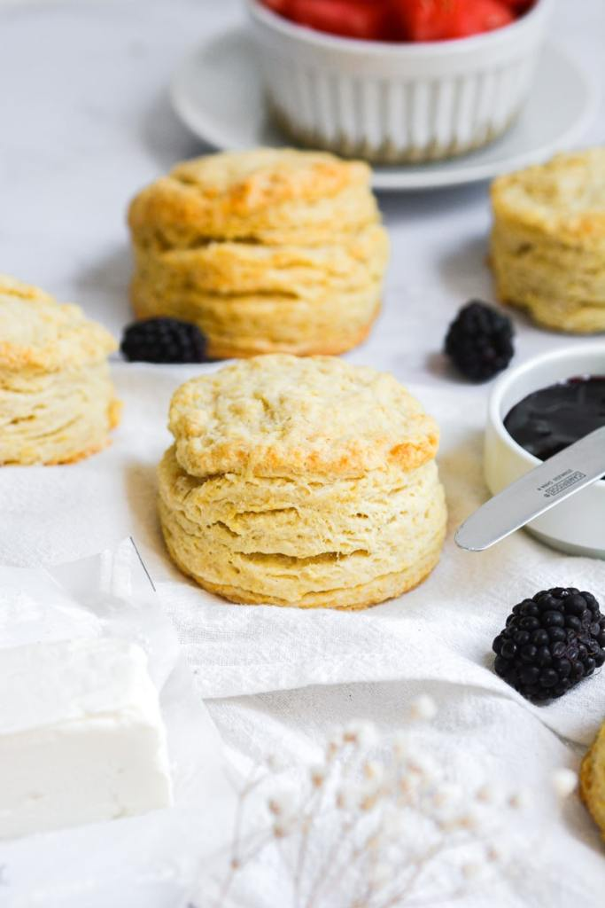 Vegan Buttermilk Biscuits on a white marble board with blackberries scattered about