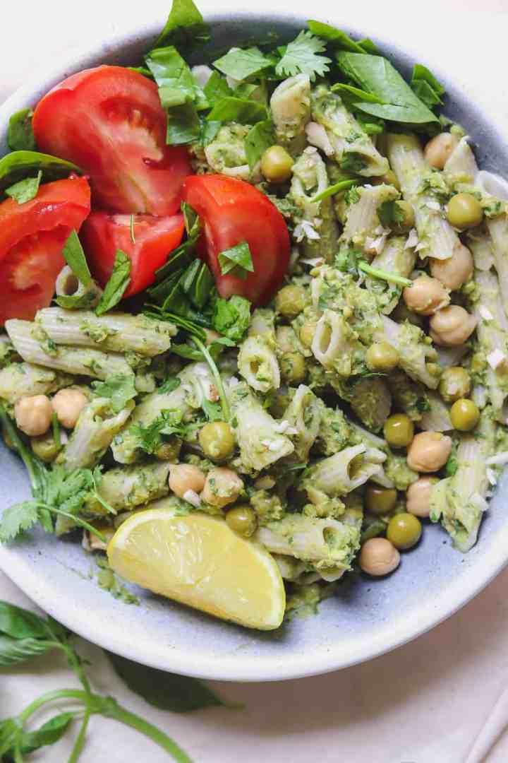 Avocado pesto pasta with green peas, chickpeas and basil