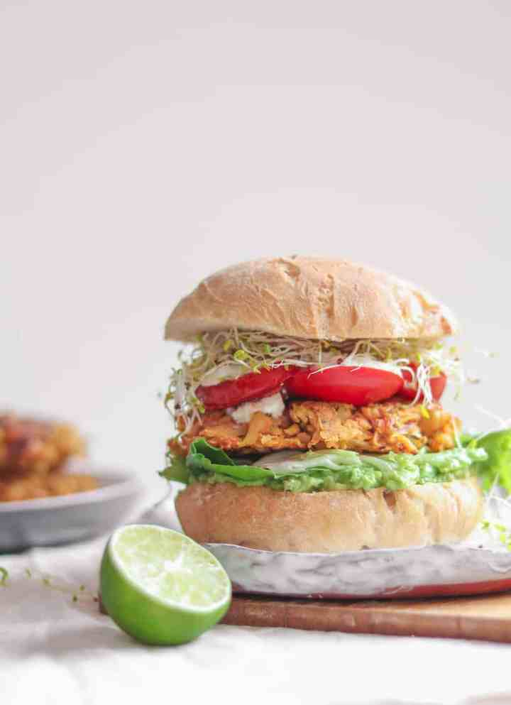 Vegan chickpea fritter sandwich with avocado, mixed greens, tomatoes, soy yoghurt and alfalfa sprouts