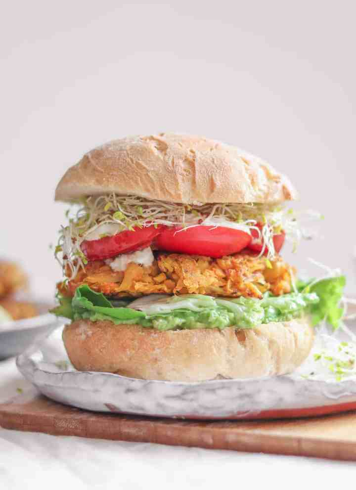 A vegan chickpea fritter burger with fresh vegetables and an avocado sauce sitting on a place before a white background