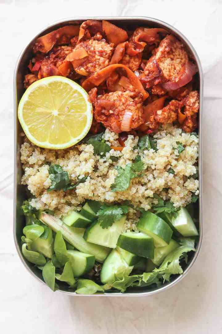 High protein meal prep lunchbox with quinoa and tempeh in a tomato sauce