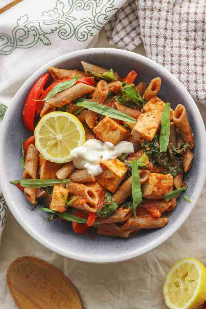Bowl of creamy vegan pasta with tomato sauce and tofu