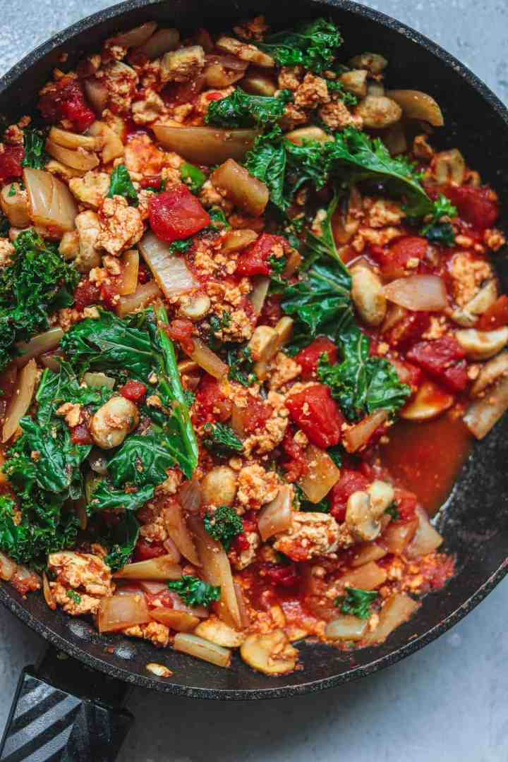 Tofu and mushrooms in a tomato sauce in a frying pan