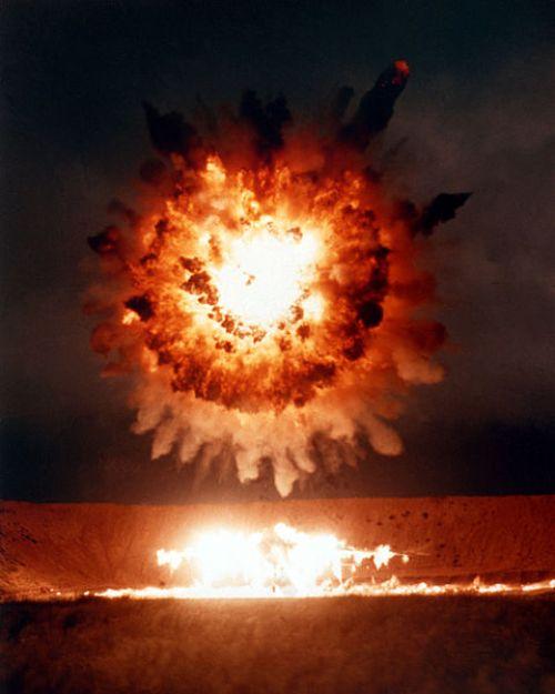 Explosão esférica brilhante de chamas e fumaça no ar.