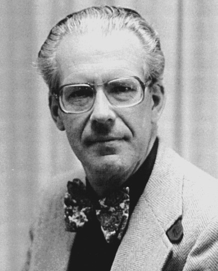 Portrait of the elderly Maarten Schmidt wearing a bow and patterned glasses.