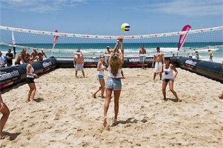 Pessoas com sombras curtas jogando vôlei em uma quadra de areia.