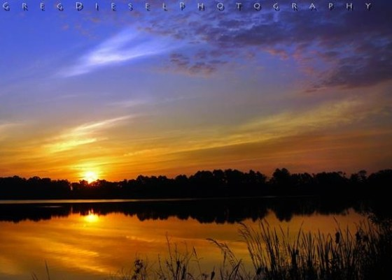 The orange-yellow sunrise under the dark blue sky was reflected in the water.