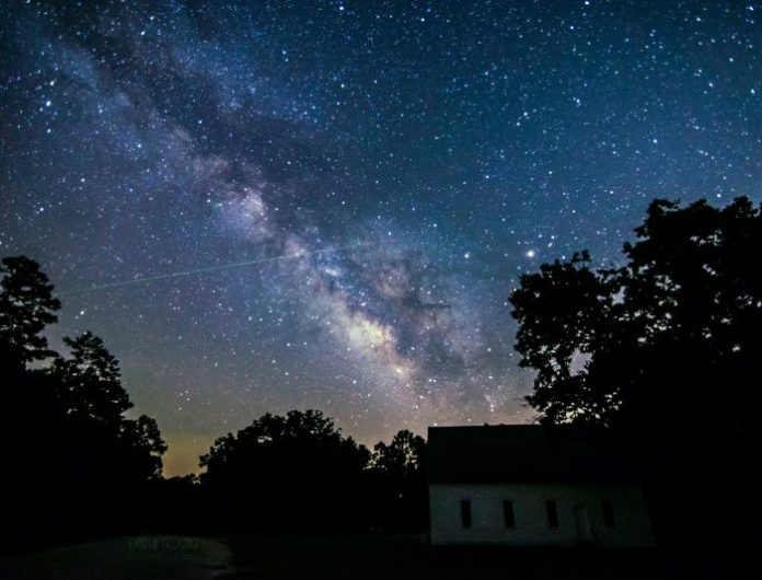 Long thin meteor trail crossing the Milky Way above trees and small house.