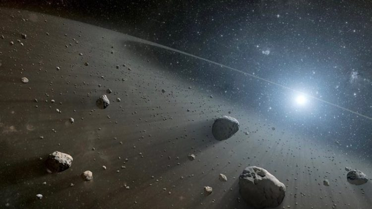 Space scene with many floating rocks illuminated with light from distant sun.