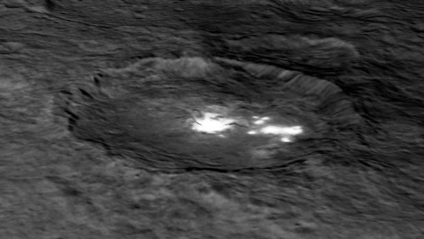 Oblique view of a pit on irregular terrain with very bright white patches.