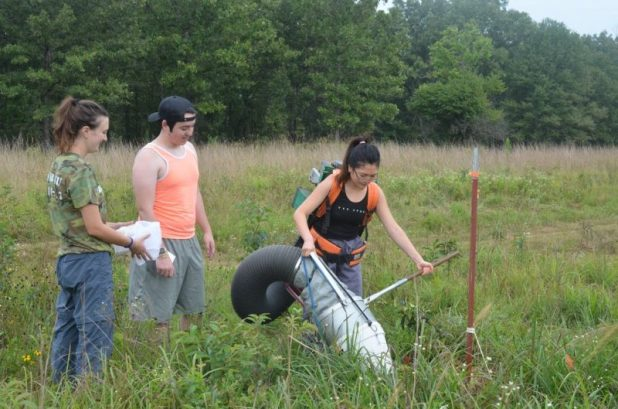 Two young women and one youth gather insects in the area with a large tube.