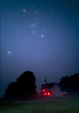 Orion and Sirius in foggy sky above an old two-story frame buildings with glowing red windows.