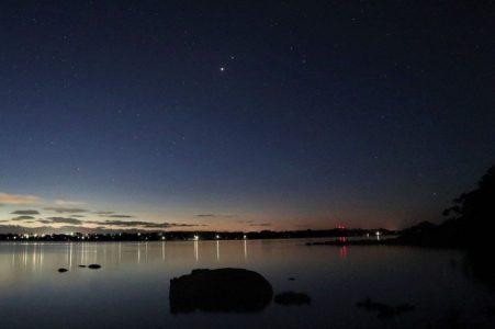 Dois pontos brilhantes juntos no céu crepuscular azul escuro sobre a massa de água.