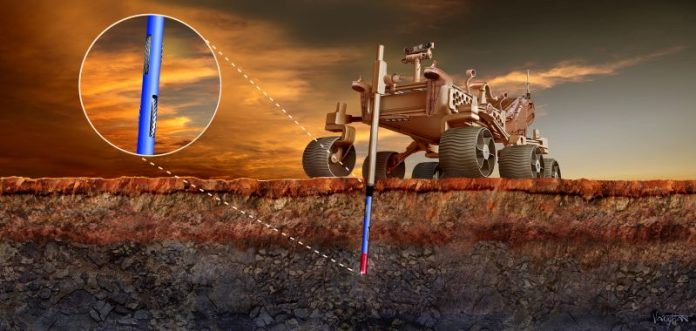 Large wheeled machine with a long probe drilling deep into reddish ground.