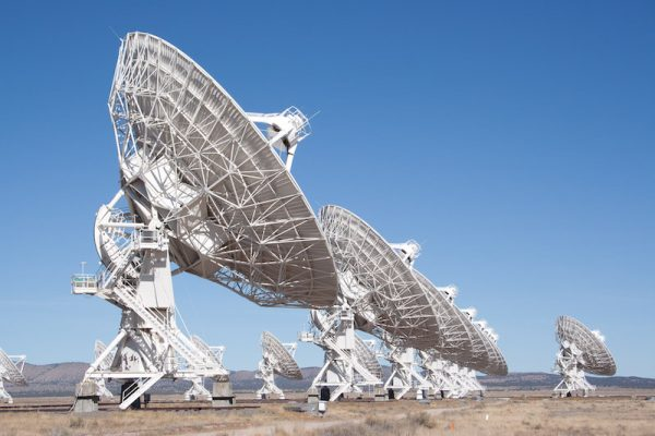 Multiple large white dish-type radio telescopes pointing to the clear blue sky.