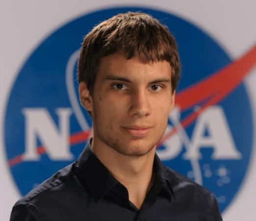Serious young man with NASA logo behind him.