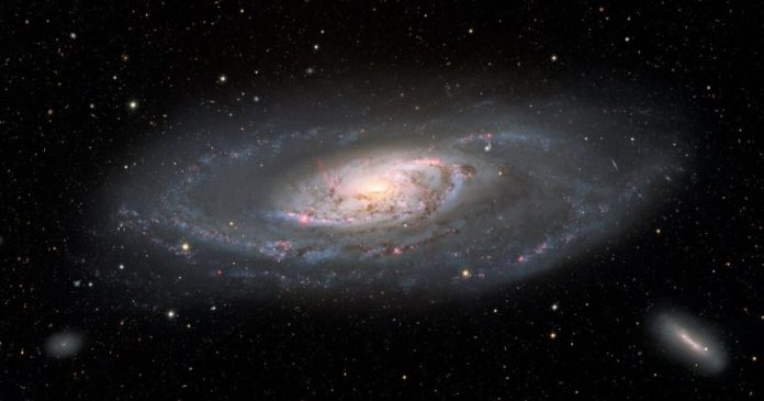 One large galaxy with spiral patterns around its bright center, with two smaller fainter galaxies in the bottom right and left corners.