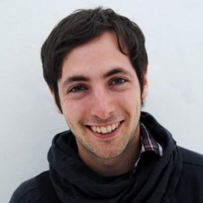 Smiling man with dark hoodie sweatshirt.