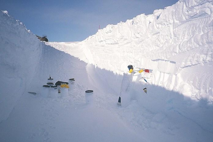 एक बड़े बर्फ की खाई में खड़े काले शीर्ष के साथ सफेद सिलेंडर।