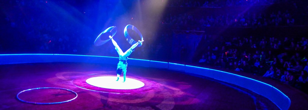 Acrobat spinning silver hoops on his legs at the Paris circus.