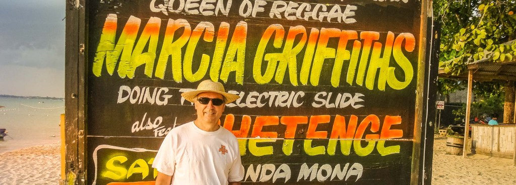 Picture of Andy in front of sign advertising Marcia Griffiths concert.
