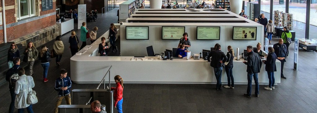 Picture of buying advance museum tickets in the Stedelijk Museum lobby.