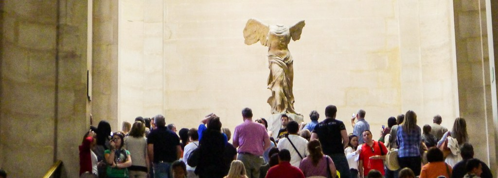 Picture of crowds viewing the Victoire statue at the Louvre.