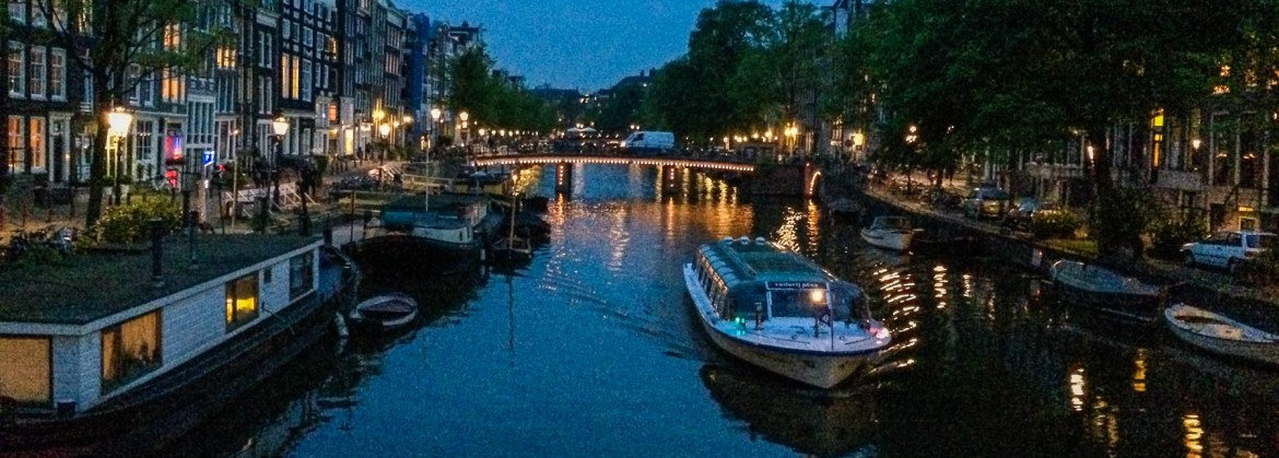 View of Amsterdam canal with Airbnb houseboat rental.