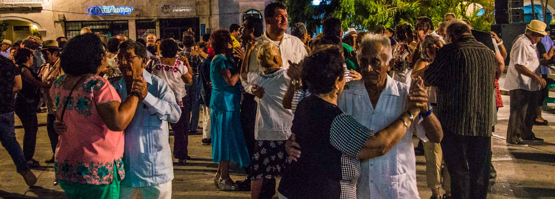 Crowd of people dancing in a park in Merida.