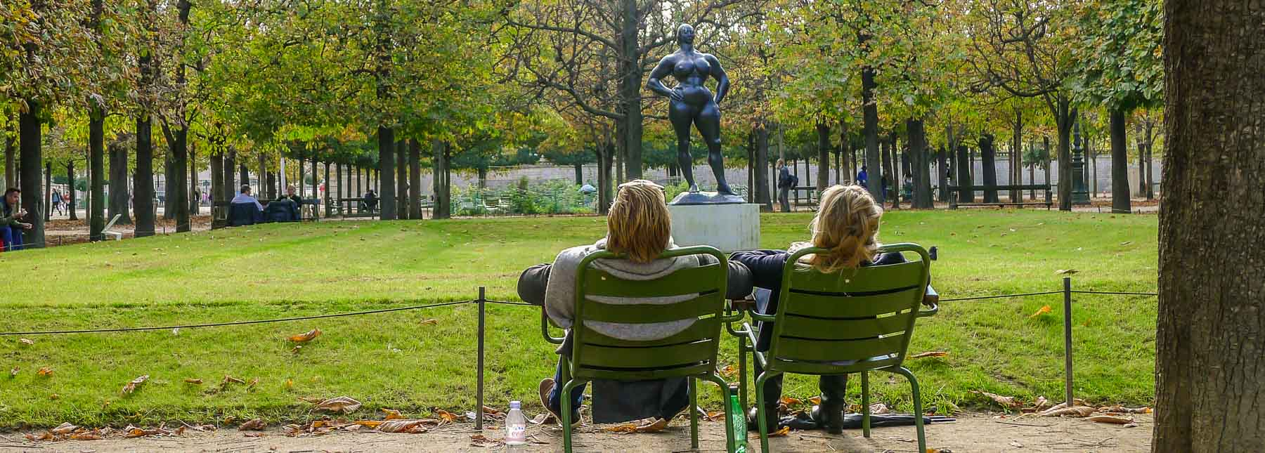 Couple in chairs looking at statue.