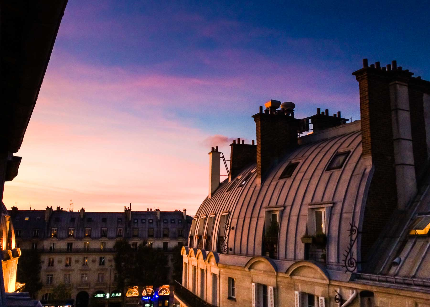 View of Paris rooftops at sunset.