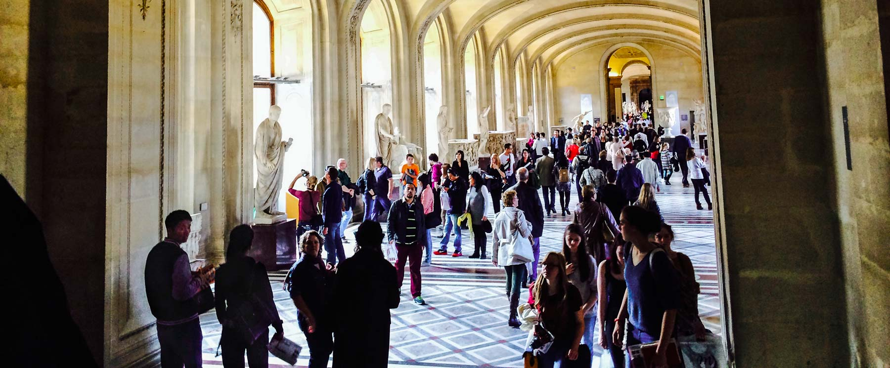 People walking in Louvre hallways.