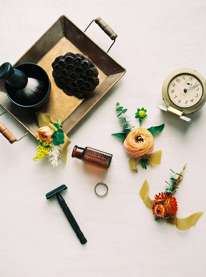 flatlay with clock flowers and tray with grooms grooming essentials