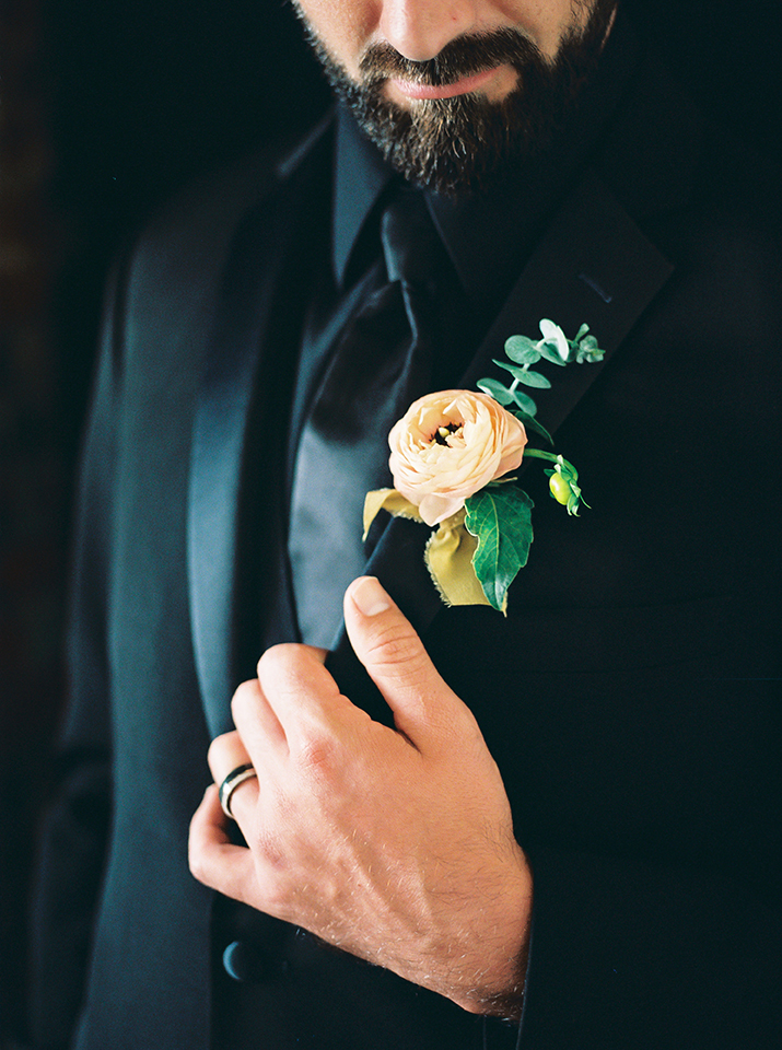 groom looking down at boutonnière while holding his suit jacket