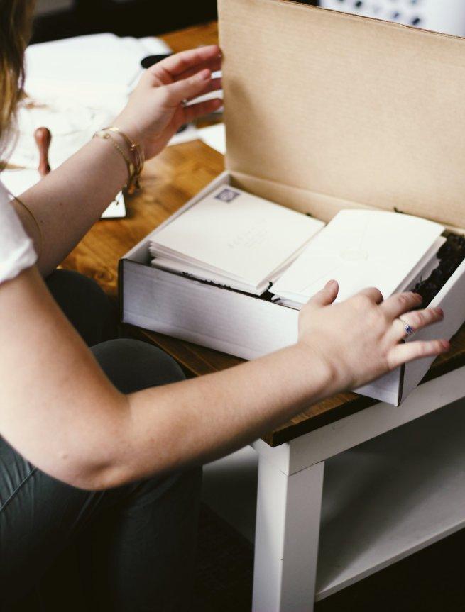 girl closing box full of wedding invitations