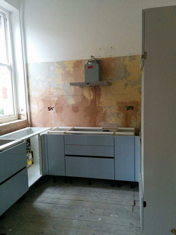 kitchen with cabinets in & first plaster fix