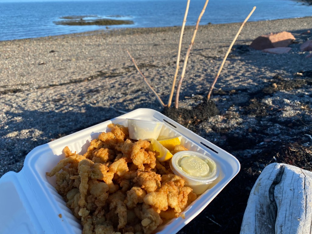 Fried clam takeout being enjoyed by Crystal Richard on the beach overlooking the ocean at sunset