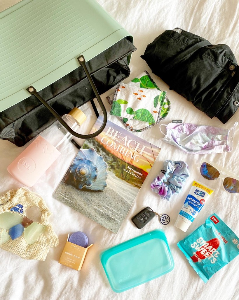 Crystal Richard's travel bag essentials laid out including a beach combing magazine, wind breaker, reusable wipes, mask, scrunchie, sunglasses, sanitizer, reusable water bottle, seaglass bag, treats.