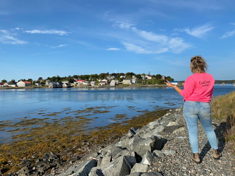 Crystal Richard standing in a pink sweater on Mulholland Point facing a view of Maine in the background