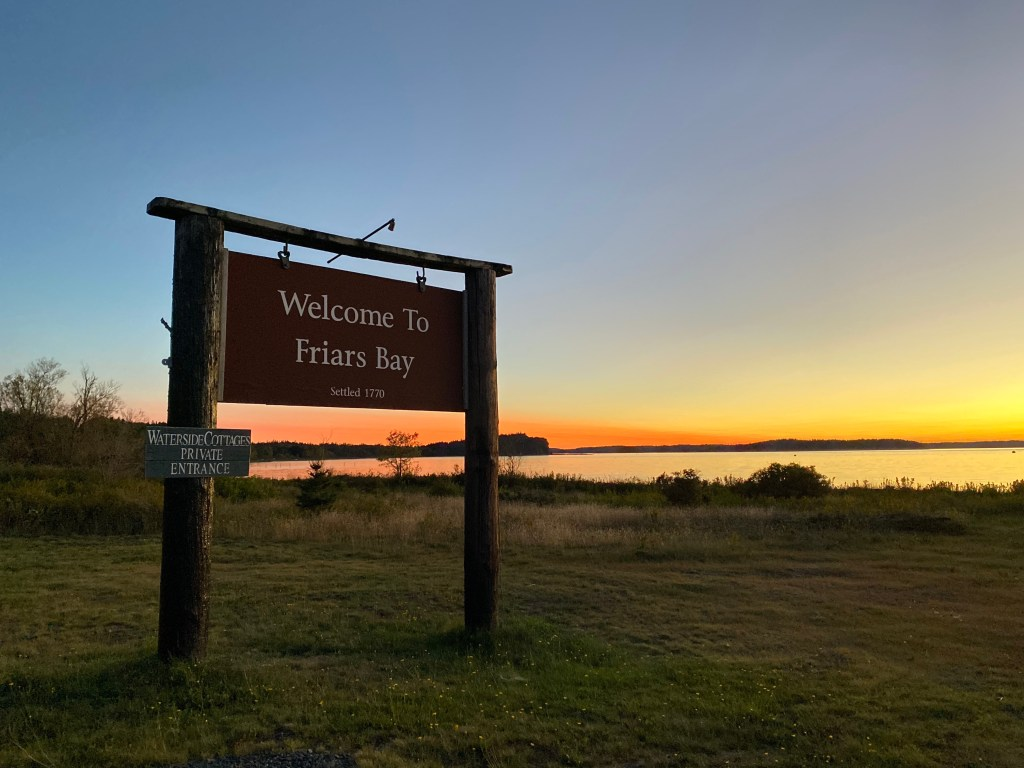 Friars Bay Inn & Cottages sign against a sunset over the ocean