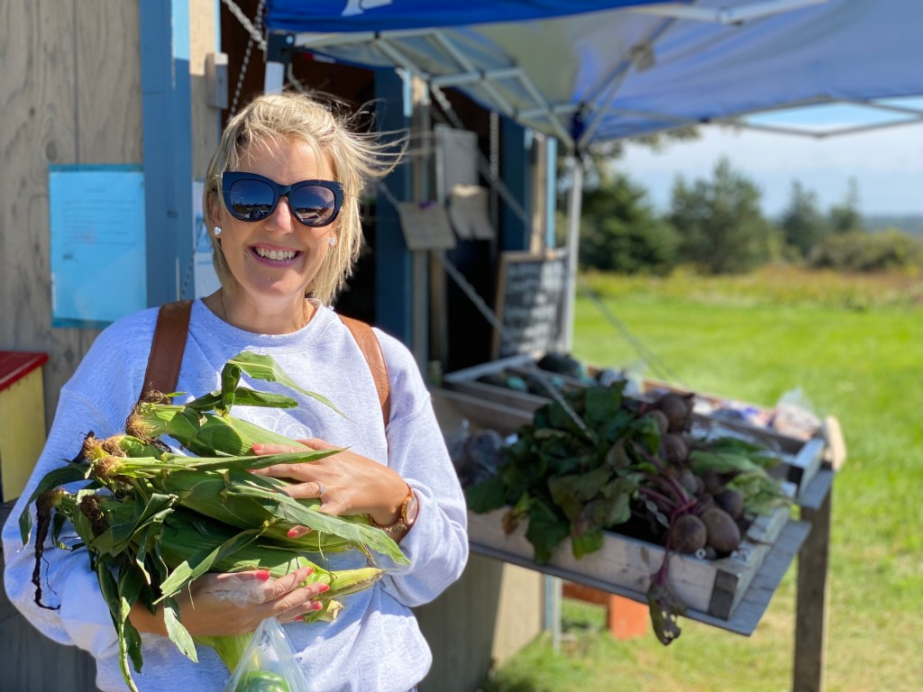 Crystal Richard with an armload of corn at The Awesome Veggie Stand, Rustico