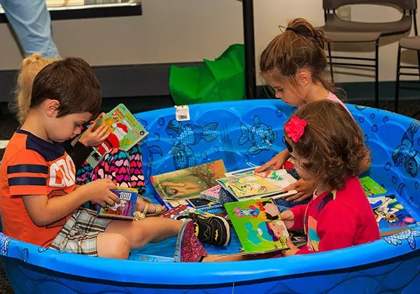 Children reading in a dry kiddie pool