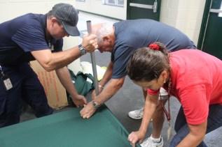 Brunswick County schools worker Terry Leffler and shelter resident Nick Dirisiu help Red Cross volunteer Ann Soeder assemble a cot